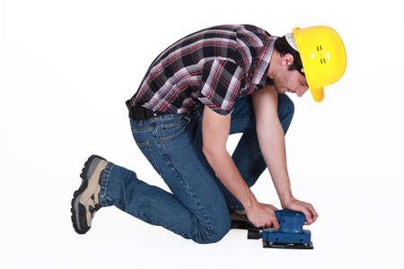 Workman using an electric sander photo