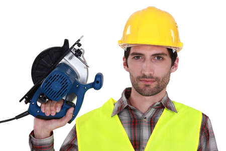poker faced: Tradesman holding a circular saw