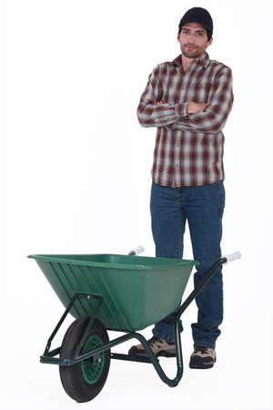 unhappy worker: Tradesman standing behind a wheelbarrow Stock Photo