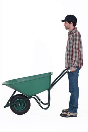 barrow: Profile shot of man stood with wheelbarrow