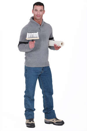 Man holding roll of wallpaper and brush photo