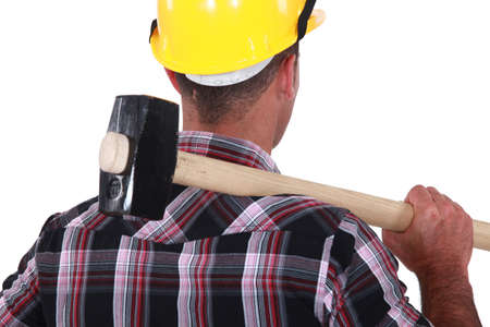 Worker resting large hammer over shoulder photo