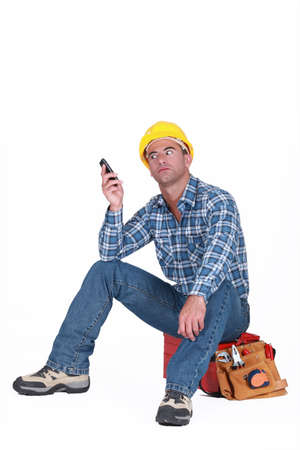 relentless: Tradesman fed up with his ringing phone Stock Photo