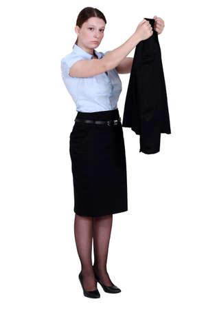 disheartened: Unhappy businesswoman hanging her blazer up Stock Photo