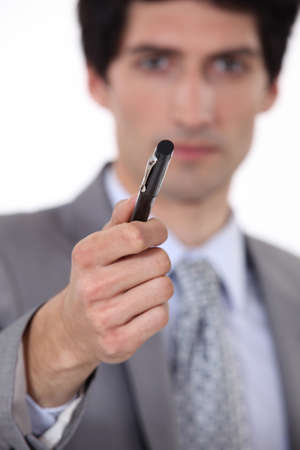filling out: businessman holding out pen for signature
