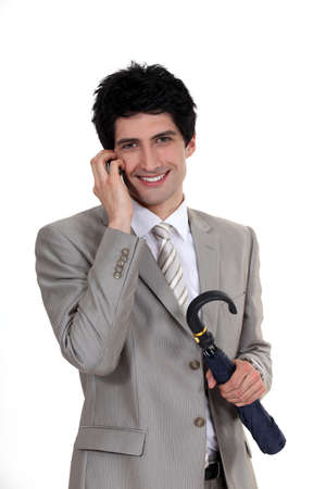 Businessman holding an umbrella and talking on a mobile phone Stock Photo - 15263858