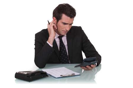 algebra calculator: Office worker using calculator Stock Photo