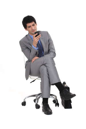 businessman waiting call: Young man in suit sending text message Stock Photo