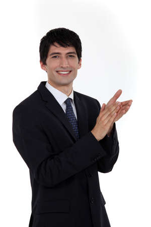 Smiling businessman clapping his hands photo