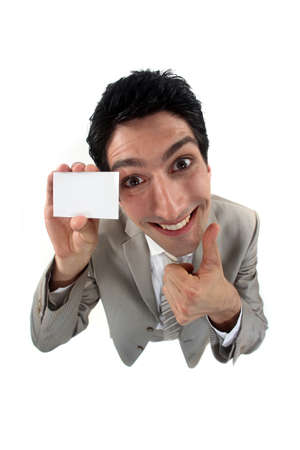 extreme angle: Grinning man holding up his business card Stock Photo