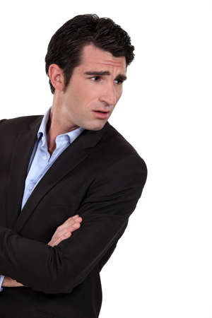 wrinkled brow: Businessman with his arms folded in disbelief Stock Photo