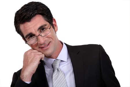 effectively: Intelligent businessman resting head on chin