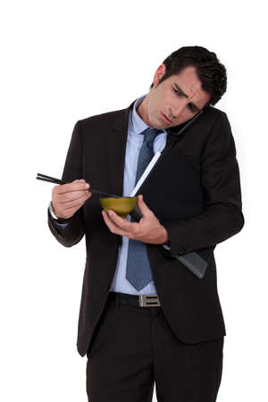 Businessman trying to eat noodles while talking on the phone photo