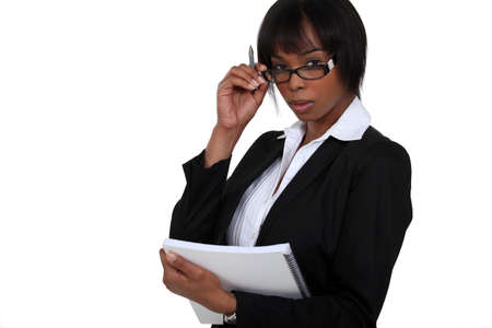 long faced: portrait of black businesswoman with glasses lowered holding notebook