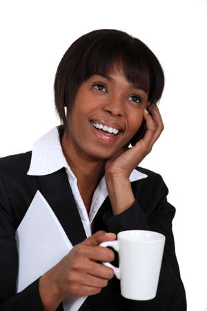 holding cell: Businesswoman chatting on the phone with a hot drink