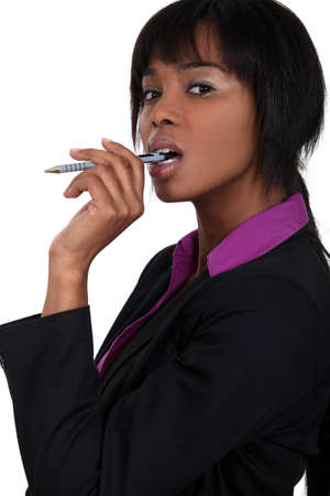 reconsider: Businesswoman chewing on pen Stock Photo