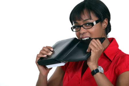 Woman biting her personal organizer Stock Photo