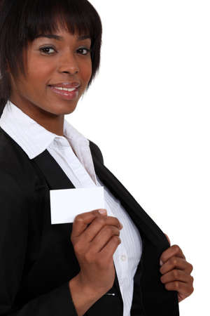 Woman pulling out a business card from her blazer photo
