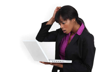 dubious: An African American businesswoman looking at her laptop with a dubious expression
