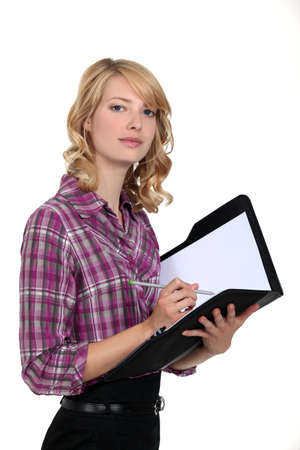 Woman writing in an office planner photo