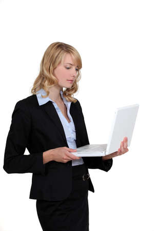 e work: Blond businesswoman stood with laptop