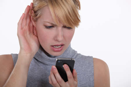 struggling: Woman struggling to have a conversation on speaker phone