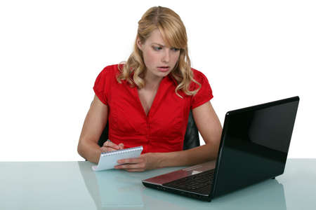 Pensive blond woman taking notes from laptop screen photo