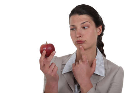 woman holding an apple and thinking photo