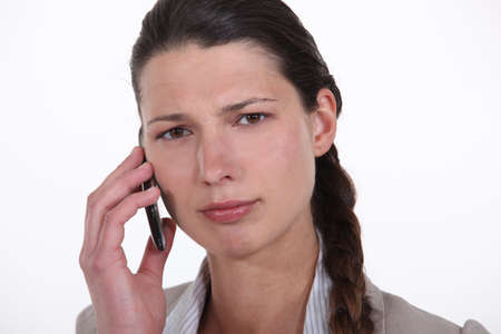 Confused woman using mobile telephone photo