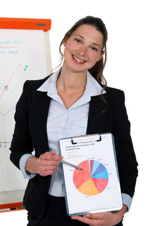 cute young businesswoman showing pie chart during meeting photo