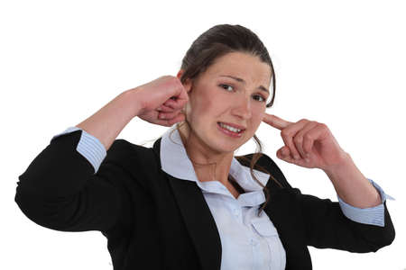 plugging: Businesswoman plugging her ears