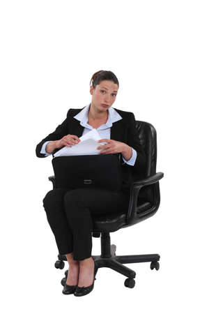 Businesswoman pulling a document out of her briefcase Stock Photo - 15289489