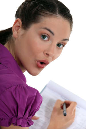 jot: Woman writing on a clipboard Stock Photo