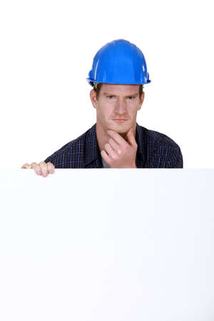 prudent: Bewildered workers behind white poster Stock Photo