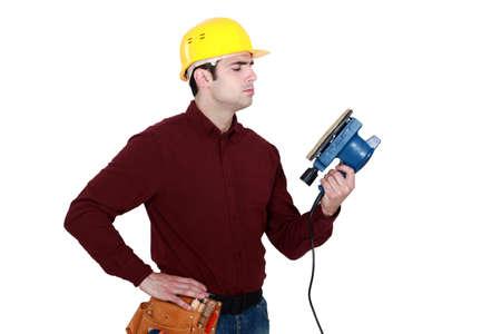 sander: Man holding electric sander
