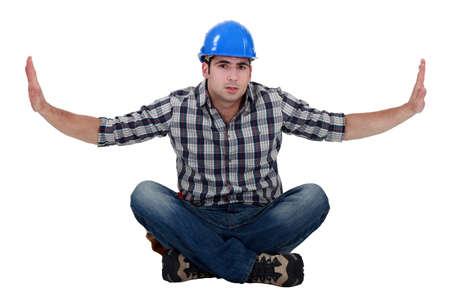 Builder sat on floor cross-legged Stock Photo - 15289878