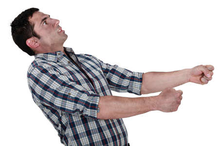 demanding: Exhausted man pulling an invisible object
