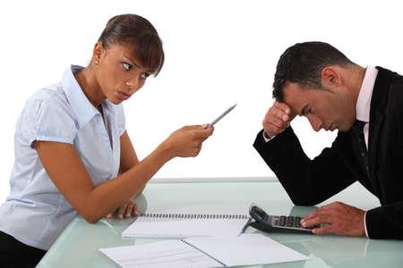 secretary desk: businessman and female colleague in disagreement Stock Photo