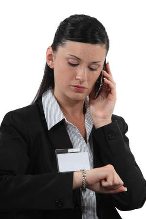 Female office worker making call and looking at watch photo