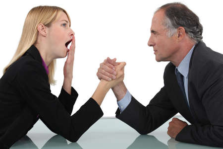 Woman arm wrestling with her boss Stock Photo