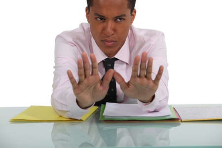 categorical: Businessman sat at desk making a stop gesture
