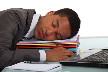 perezoso: Trabajador que duerme en una pila de carpetas Foto de archivo