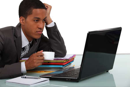25 30: Young businessman taking a break in front of his laptop Stock Photo