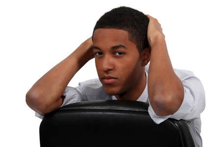 run down: Bored young businessman sat on office chair