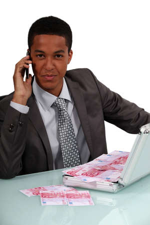 corporate greed: Young businessman with briefcase full of money Stock Photo