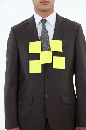 Businessman covered in yellow memo pads photo