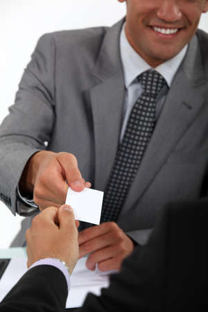 personalised: Businessman handing over his business card to a potential client Stock Photo