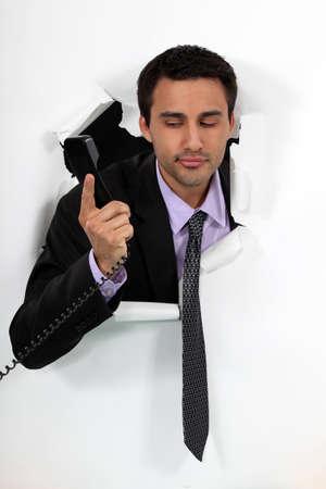 bursting: Businessman looking at a telephone handset Stock Photo