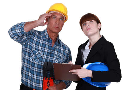 perceptive: Tradesman and engineer looking at the ceiling