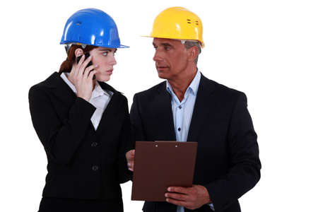 Couple in business suits and hardhats Stock Photo - 15289591